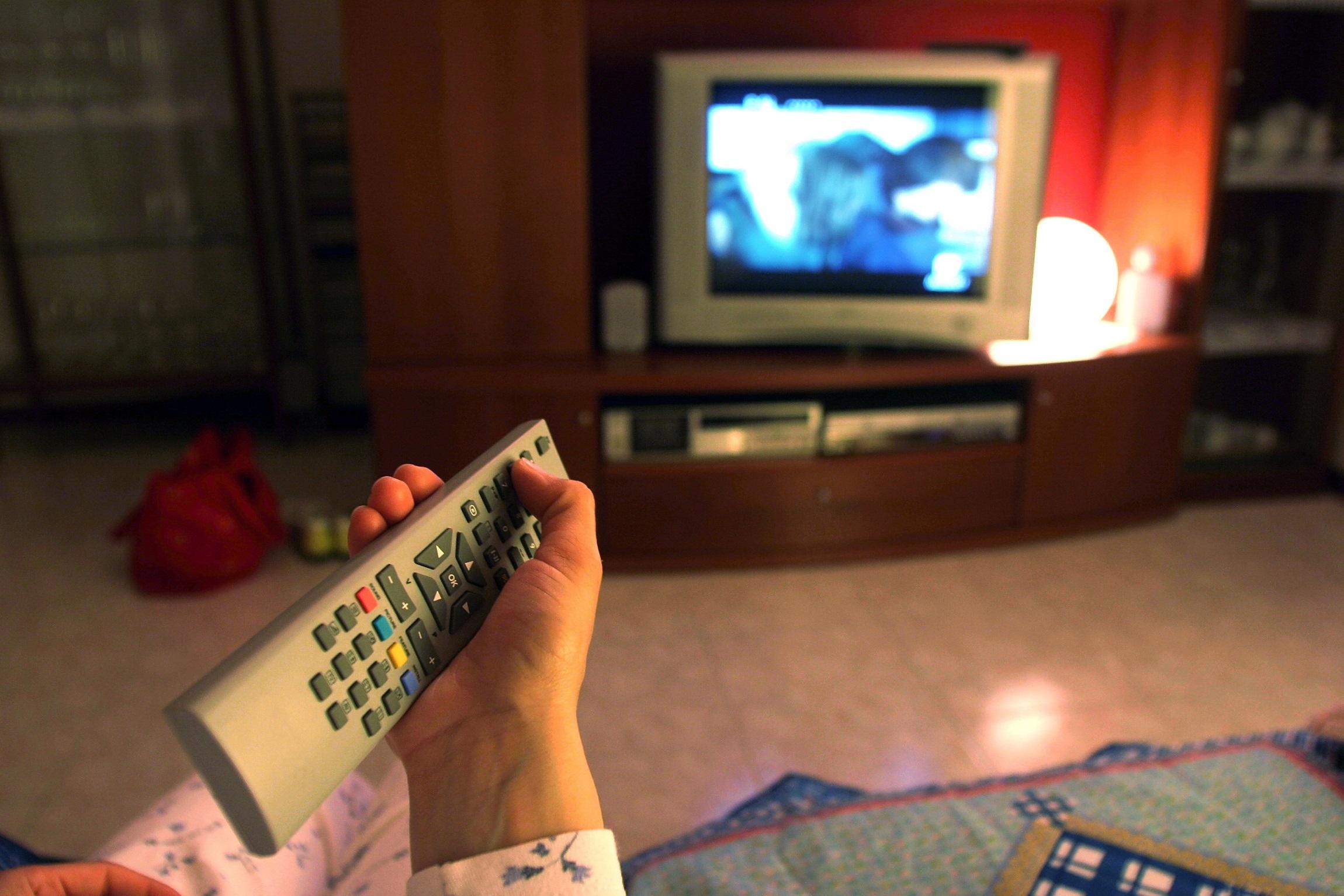 DONNA GUARDA LA TELEVISIONE, TELECOMANDO, TELEVISORE